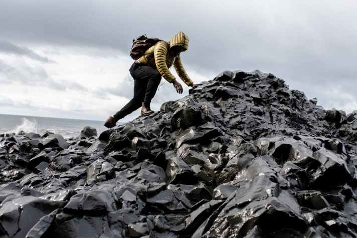 man wearing hoodie and black pants climbing up pile of rocks