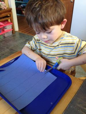 kid cutting chain paper